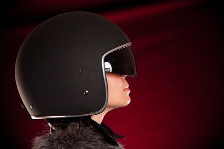 Biker girl in a helmet on a red backgroundの写真素材