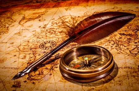 Vintage magnifying glass and compass lying on an old map.