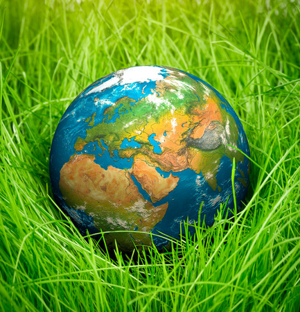 Globe lies on green grass. Concept - Earth Day.