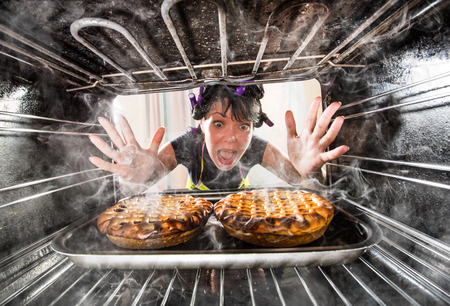 Photo pour Funny Housewife overlooked cakes in the oven, so she had scorched, view from the inside of the oven. Housewife perplexed and angry. Loser is destiny! - image libre de droit