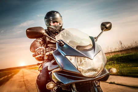 Photo for Biker in helmet and leather jacket racing on the road - Royalty Free Image