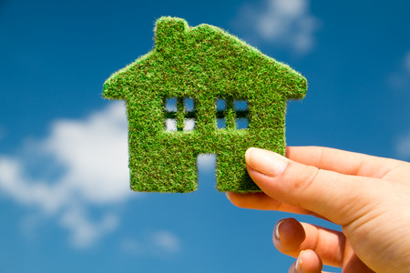 Photo pour Grass home on a background of blue sky in human hands - image libre de droit