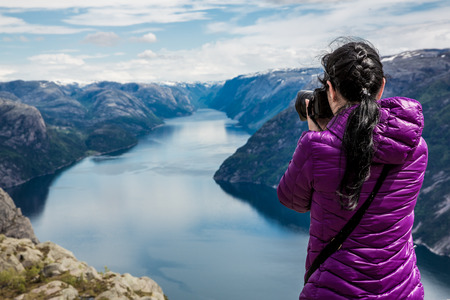 Photo for Nature photographer tourist with camera shoots while standing on top of the mountain. Beautiful Nature Norway Preikestolen or Prekestolen. - Royalty Free Image