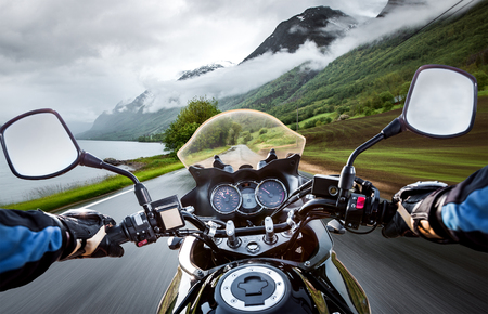 Biker rides a motorcycle in the rain. First-person view.