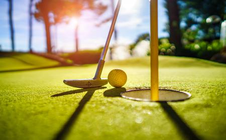 Photo pour Mini Golf yellow ball with a bat near the hole at sunset - image libre de droit