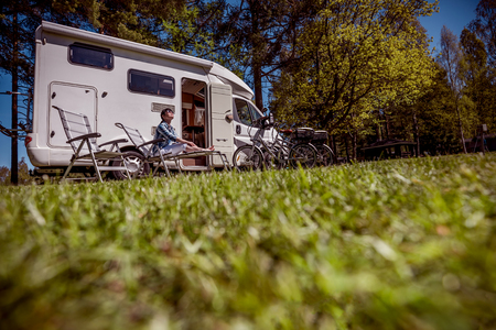 Photo pour Woman resting near motorhomes in nature. Family vacation travel, holiday trip in motorhome RV, Caravan car Vacation. - image libre de droit