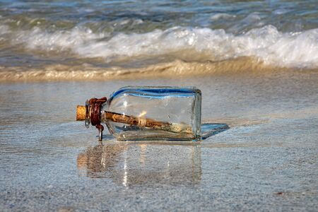 Photo pour Message in the bottle against the Sun setting down - image libre de droit