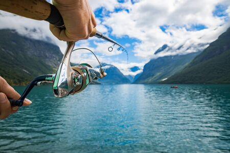 Photo pour Woman fishing on Fishing rod spinning in Norway. Fishing in Norway is a way to embrace the local lifestyle. Countless lakes and rivers and an extensive coastline means outstanding opportunities... - image libre de droit