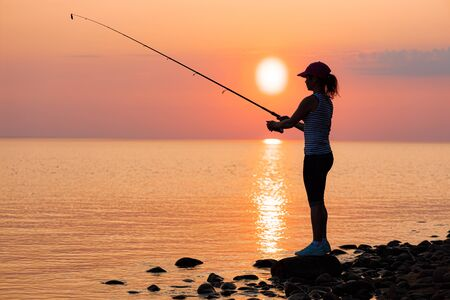 Photo pour Woman fishing on Fishing rod spinning at sunset background. - image libre de droit
