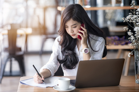 Photo for young asian business woman using laptop and writing on notebook, woman officer hard working communicate with customer and record - Royalty Free Image
