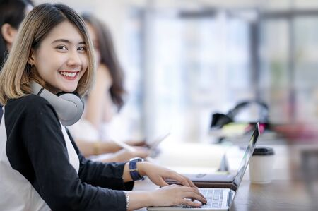 Photo pour Portrait of young woman smiling and looking at camera while working in modern office with her friends. - image libre de droit