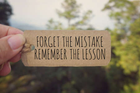 Photo pour Motivational and inspirational quote - 'Forget the mistake, remember the lesson' written on a paper tag. Vintage styled background. - image libre de droit