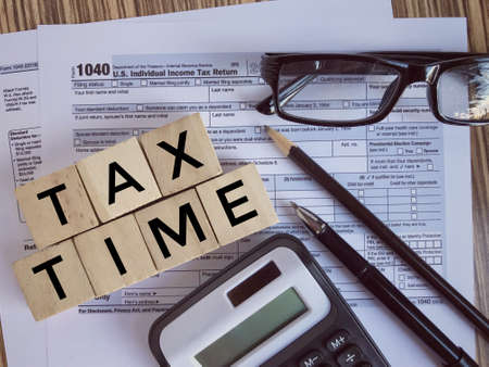Photo pour United States federal income tax return IRS 1040 documents, with pen, pencil, calculator,eyeglasses and wooden blocks with 'TAX TIME' written on them. - image libre de droit