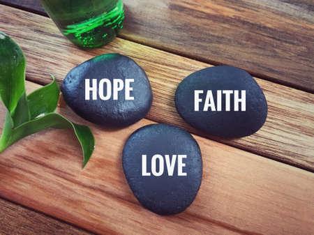 Photo pour Inspirational wording - HOPE, FAITH, LOVE written on pebbles. - image libre de droit