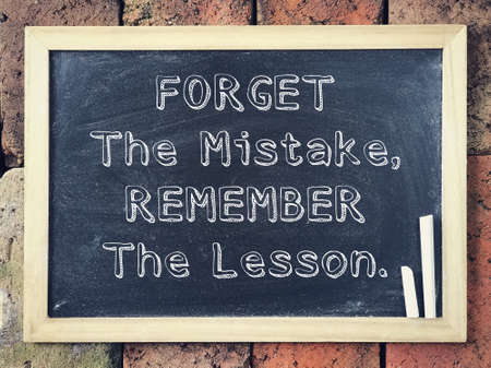Photo pour Motivational and inspirational wording - Forget The Mistake, Remember The Lesson written on a black board. - image libre de droit