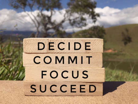 Photo pour Motivational and inspirational wording - Decide, Commit, Focus, Succeed written on wooden blocks. Blurred styled background. - image libre de droit