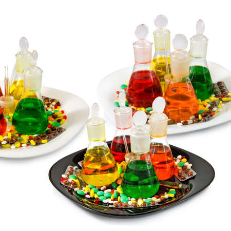 flasks with colored liquid and pills on white background
