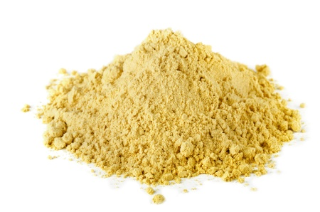 Pile of dry mustard powder spice isolated on white