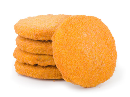 Stack of frozen breaded fish patties isolated on white