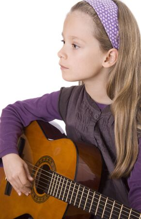 Young girl with long hair is playing guitar.