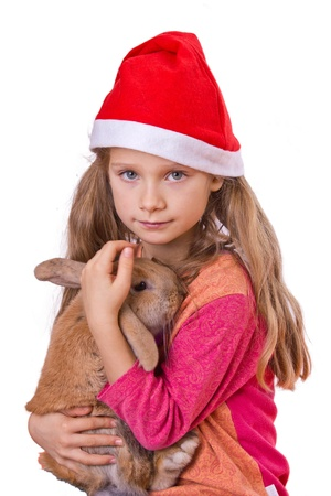 girl on christmas with a red cap and a rabbit