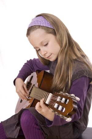 A young girl with long hair is playing guitar.