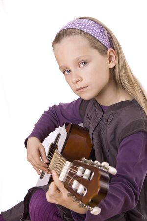 A young girl is playing her guitar.
