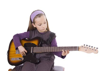 A young girl is playing guitar.