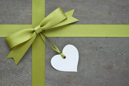 green loop with white heart on wooden ground