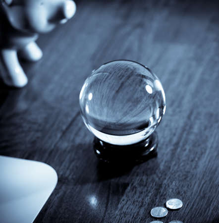 Concept:  Financial guessing game with piggy bank, crystal ball and coins in cold tones.