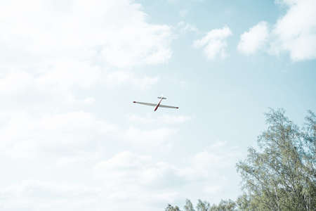 A glider flying on a sunny day against a blue sky