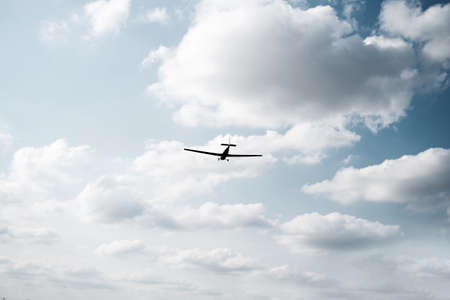 A plane flying on a sunny day against a blue sky