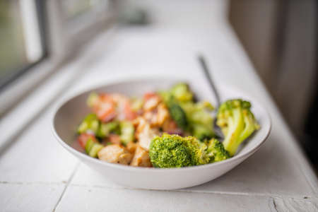Photo pour Broccoli and chicken salad on white bowl next to a window - image libre de droit