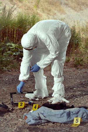 Photo for Criminologist technician in DNA free protective suit collecting evidences of probable criminal act - Royalty Free Image