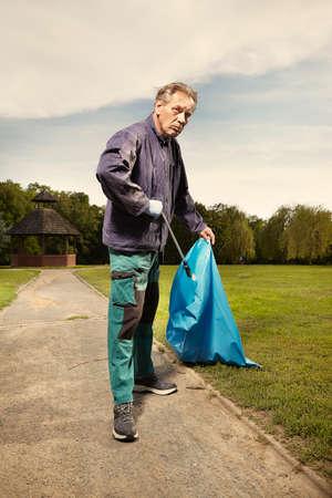 Photo pour Man in public service cleaning up trash in city park - image libre de droit