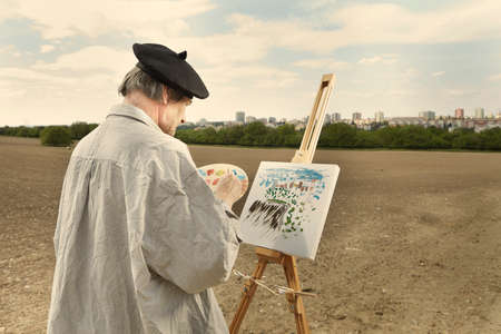Foto de Older man painting artwork on canvas in sunny day field - Imagen libre de derechos