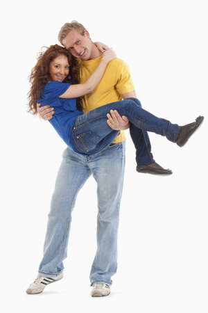 happy young couple - boy carrying girl in his arms - isolated on white