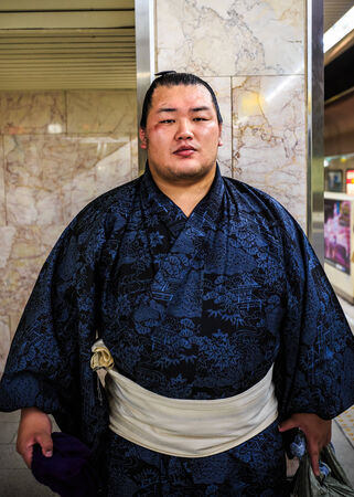 FUKUOKA, JAPAN - NOVEMBER 13: Sumo wrestler in Fukuoka, Japan on November 13, 2013. Unidentified Japanese Sumo wrestler waits for a train to his tournament at Fukuoka Sumo arena