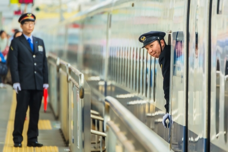 OKAYAMA, JAPAN - NOVEMBER 17  Train Conductor in Okayama, Japan on November 17, 2013  Unidentified Japanese train conductor observes passenger before giving a sign to move the train
