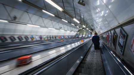 London, UK - May 20 2018:  Unidentified people travel through underground train network at South Kensington station subway in London