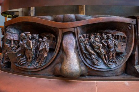 London, UK - May 14 2018: Deatils on the base of The Meeting Place, 9-metre bronze statue revealed in 2007, stands at the south end of the upper level of St Pancras railway station by British artist Paul Day
