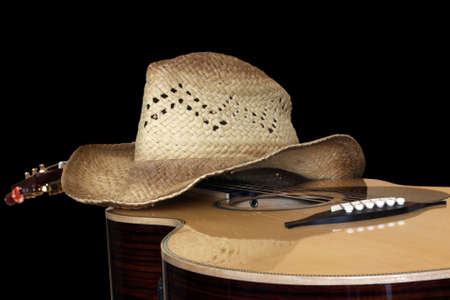 acoustic guitar with hat isolated on black