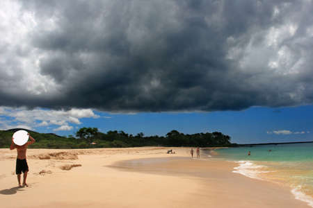 Surfer getting ready for a powerful storm above Makena beach in Hawaii