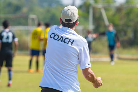 Photo for Back view of male football coach in white COACH shirt at an outdoor football field giving direction to his football team - Royalty Free Image