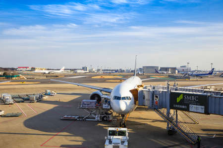 Photo for Tokyo, Japan - 24 April 2019 - International airplane waits for its passengers to board while loads in cargo at Tokyo airport, Japan on April 24, 2019 - Royalty Free Image