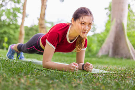 Foto de Beautiful young Asian woman stretching planking during her morning exercise on her yoga mat at a park on a clear sunny sky day, healthy lifestyle, copy space - Imagen libre de derechos