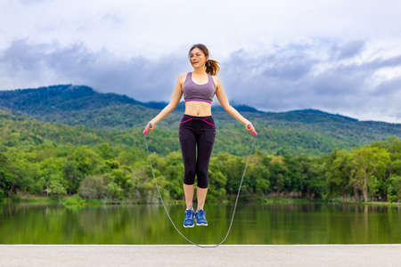 Foto de Beautiful happy young Asian woman jumping rope during her morning exercise at a lake with mountains background, healthy lifestyle - Imagen libre de derechos