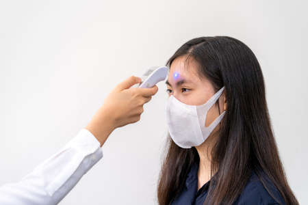 Photo pour Young Asian woman wearing N95 mask, getting her temperature check - health concept - image libre de droit