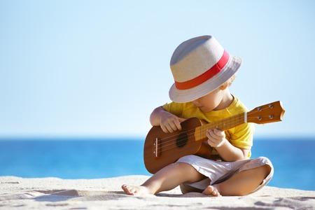 Little boy plays guitar ukulele at sea beach