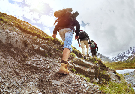 Foto de Group of three tourists walking uphill by trek in mountains - Imagen libre de derechos